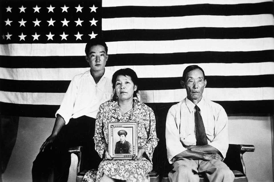 Risa and Yasubei Hirano and their son George posed in front of an American flag